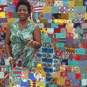 Olutosin Oladusa Adebowale standing in front of a patchwork quilt.